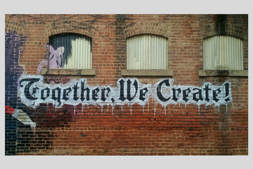 "Photo of graffiti on brick wall saying ""Together we create!"""