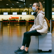 Student wearing a mask at an airport