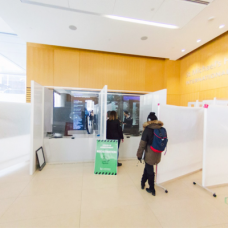 Healthcare workers stand behind the ASTOUND Group's plexiglass protective booths while talking with patients at St. Michael's Hospital Assessment Centre in Toronto.