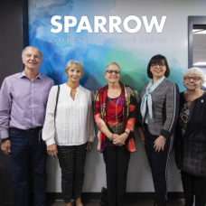 Five people standing in front of the Sparrow sign