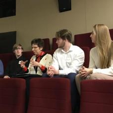 Students listening to a teacher during a classroom seminar.