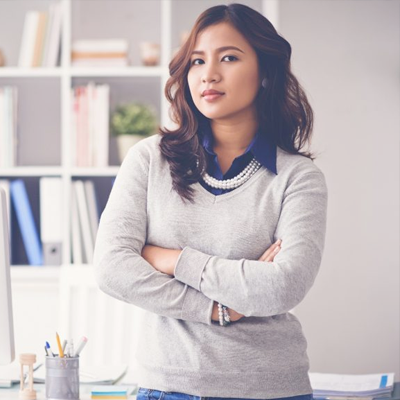 Woman standing with her arms crossed posing in front of a work station