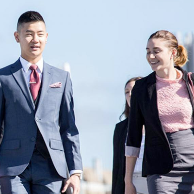 Students wearing suits walking towards a building