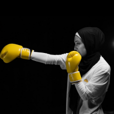 Student wearing yellow boxing gloves
