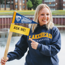 Lakehead University student holding up an orientation sign
