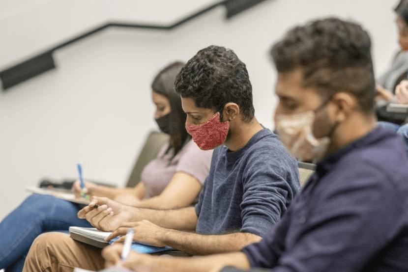 Students wearing masks in university auditorium